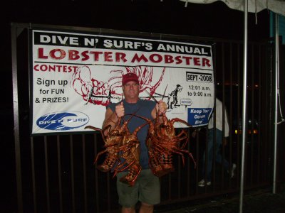 A guy poses with his huge lobsters.