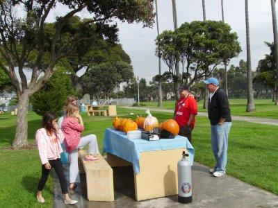 The judges judge the pumpkins.
