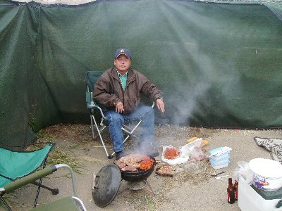 Instructor Ed mans the barbecue, adhering to strict food preparation laws.