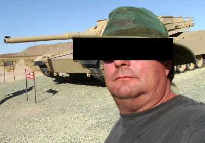 A person in front of a tank.